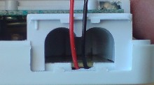 Wires emerging from the thermostat out of a groove cut out of the plastic.