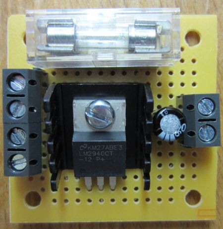 MINI 12 VOLT REGULATOR WITH FUSE AND SWITCH TERMINALS. Supply a fixed 12.0 Volt DC to your devices (up to 1 Amp output). Includes fitted 1A fuse, 2 spare fuses, and terminals for connection of a switch